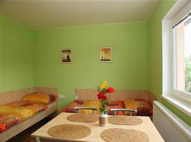 Obytná místnost s lůžky a jídelním stolem