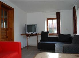 Obývací pokoj se sedačkami a televizí