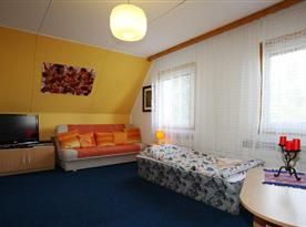 Obývací pokoj s lůžky a televizí