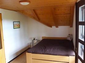 Mezonetový apartmán - ložnice s manželskou postelí a posezením na balkoně