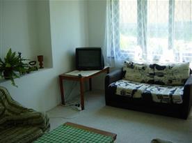 Obývací pokoj se sedací soupravou, gaučem, stolkem a televizí