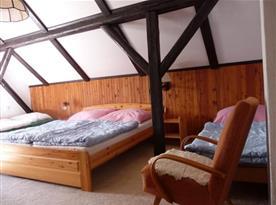 Podkrovní pokoj s lůžky, pohovkou, stolkem a křesly