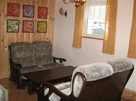 Společenská místnost se sedací soupravou, stolkem a televizí