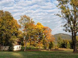 Pohled na chatu s horou Špičák v pozadí.