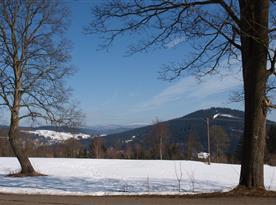 Panoramatický pohled z chaty na horu Špičák, Jizerské hory a v povzdálí i Krkonoše.
