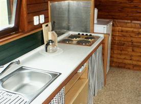 Kuchyně s varnou deskou, lednicí, varnou konvicí a mikrovlnou troubou