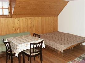 Podkrovní pokoj s lůžky stolem a židlemi