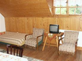 Podkrovní pokoj s lůžky, stolem, židlemi a televizí