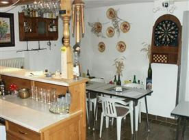 Bar s výčepem, stoly, židlemi a šipkami