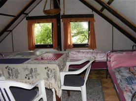 Podkrovní ložnice s lůžky, stolem, židlemi a věšáky