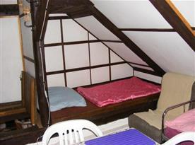 Podkrovní ložnice s lůžky, stolem, židlemi, křěslem a věšáky