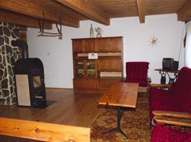 Obývací pokoj se sedací soupravou, stolem, skříní, kamny a televizí