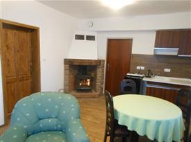 Společenská místnost 1 s televizí, sedačkou, jídelním stolem a krbovými kamny