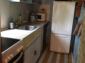 Kuchyňský kout se sporákem, lednicí, varnou konvicí a mikrovlnou troubou