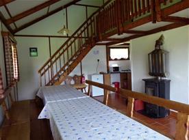Společenská místnost se stoly , lavicemi a schody do podkroví