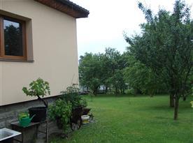 Zahrada s ovocnými stromy kolem domu