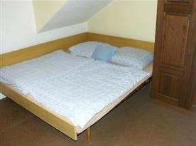 Pokoj s lůžky, skříní, poličkou a lampičkou