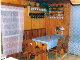 Obytná místnost se stolem, židlemi, kamny a gaučem
