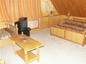 Podkrovní ložnice s lůžky, stolkem, skříní a televizí