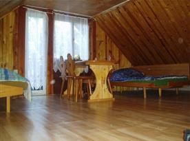 Ložnice s lůžky, stolem, židlemi, skříňkou a vstupem na balkón