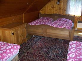 Podkrovní pokoj s lůžky, skříňkou a lampičkou