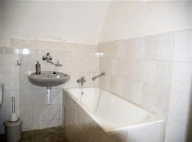 Koupelna s vanou, toaletou a umyvadlem v apartmánu