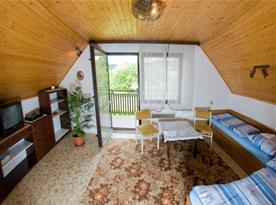 Podkrovní obývací ložnice s lůžky,stolem, židlemi, televizí a vstupem na balkón