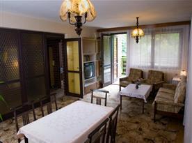 Obývací pokoj se sedací soupravou, stolkem, televizí a vstupem na balkón