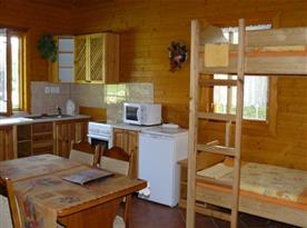 Čtyřlůžková chata - interiér obytné místnosti s kuchyní, jídelnou a palandou