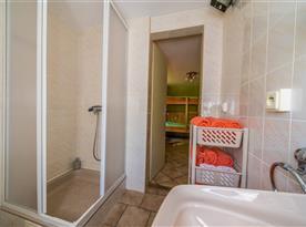 Koupelna s umyvadlem a sprchou