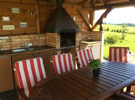 Posezení pod dřevěnou pergolou s krbem a venkovní kuchyní