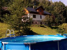 Pohled od bazénu na chalupu