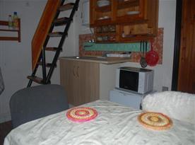Kuchyňský kout v suterénu s lednicí, vařičem a mikrovlnnou troubou