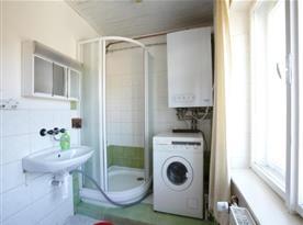 Koupelna se sprchovým koutem, toaletou, pračkou a umývadlem