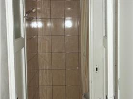 Sociální zařízení se sprchou, umývadlem a zrcadlem