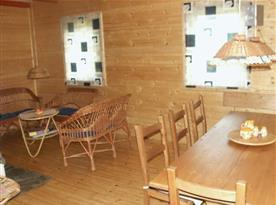 Společenská místnost s ratanovým nábytkem, krbem a televizí