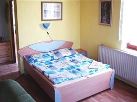 Obývací pokoj s lůžky, nočními stolky a křesly