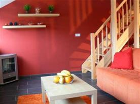 Obývací pokoj s krbem a schody do podkroví