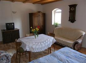 Pokoj s lůžky, sedací soupravou a televizí