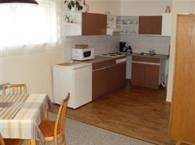 Pohled na kuchyňský kout s mikrovlnou troubou, lednicí, vařičem a kuchyňským stolem