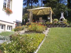 Pohled od bazénu - terasa s krytým posezením zahradním krbem