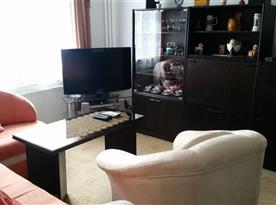 Pokoj s rozkládací rohovou sedačkou a televizí se satelitem