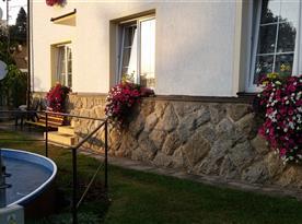Pohled na dvůr s bazénem, zahradním nábytkem a houpačkou