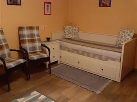 Společenská místnost s televizí, komodou, křesílkami, skříní