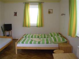 Pokoj s lůžky, nočním stolkem, televizí a koupelnou