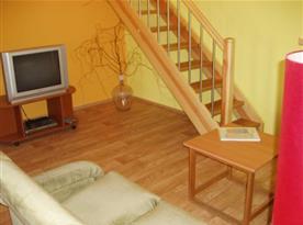 Obyvací pokoj apartmánu B s posezením a televizí