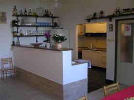 Společenská místnost s barovým pultem a kuchyňkou