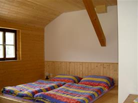 Pokoj obložený dřevem v podkroví