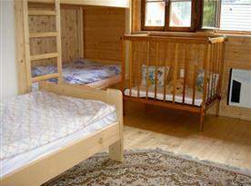 Pokoj s lůžky a dětskou postýlkou