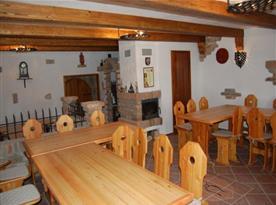 Velká společenská místnost se stoly, židlemi a krbem
